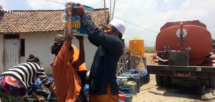 BANTU WARGA: Petugas BPBD Kabupaten Situbondo distribusikan air bersih kepada masyarakat yang dilanda kekeringan akibat kemarau panjang. (imam)