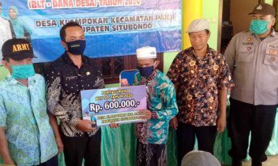 SIMBOLIS: Kepala Desa Klampokan Adi Arso saat menyalurkan BLT - DD Tahap II Tahun 2020 kepada KPM penyandang disabilitas Desa Klampokan, Kecamatan Panji, Kabupaten Situbondo, Jawa Timur. (her)