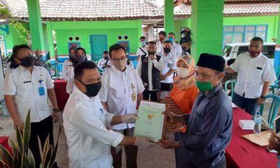 Wakil Bupati Situbondo Ir H Yoyok Mulyadi M Si secara simbolis menyerahkan sertipikat hak atas tanah kepada sejumlah nelayan penerima. (her/im)