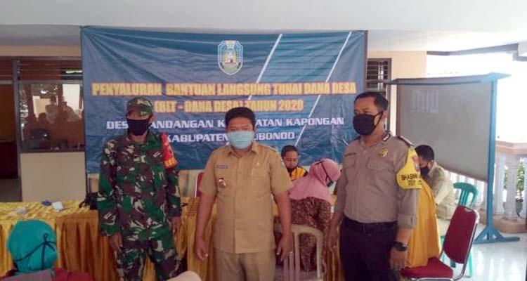 Kepala Desa Landangan, Kamilul Maarif diapit Babinsa dan Babinkamtibmas saat memberikan sambutan pada penyaluran BLT-DD tahap III. (im)