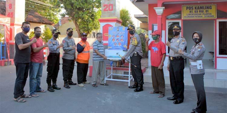 Kapolres Situbondo AKBP Sugandi SIK M Hum memberikan bantuan tempat cuci tangan, herbal prebiotic dan obat Lianhua kepada warga KTS dilingkungan Plaosa. (im)