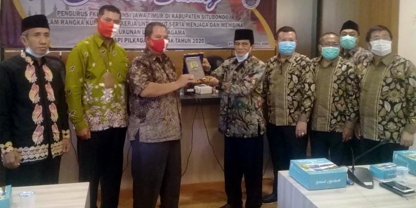 Ketua FKUB Kabupaten Situbondo KH Yusron Samrowi didampingi oleh Kepala Bakesbangpol Edy Wiyono saat memberikan cindera mata kepada Ketua FKUB Jawa Timur (Jatim) A Hamid Syarif di ruang Baluran Pemkab Situbondo. (her)