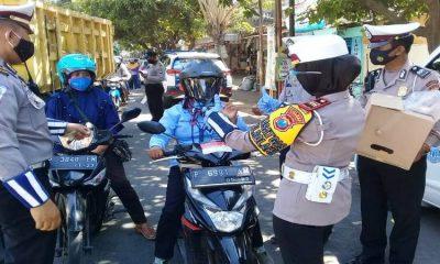BERIKAN REWARD : Kasat Lantas Polres Situbondo AKP Indah Citra Fitriani SIK saat memberikan helm gratis pada pengendara sepeda motor yang tertib. (im)